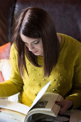 Attractive brunette woman student reading/ studying in her room