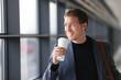 Businessman drinking coffee walking in airport