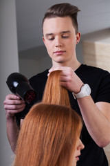 Hairdresser is drying customer hair