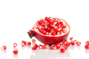 Pomegranate with seeds over white