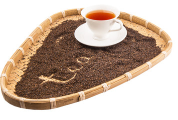 A cup of tea in a wicker tray with written TEA word on dried tea