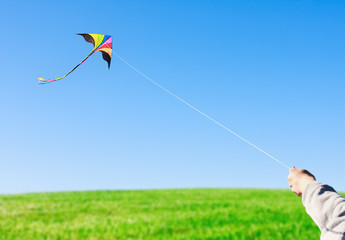 hand holding a kite against the sky