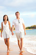 Casual couple walking on beach holding hands