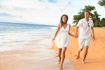 Beach couple on romantic travel honeymoon fun