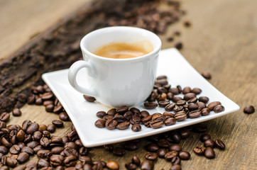 A cup of espresso and coffee beans on old wooden board