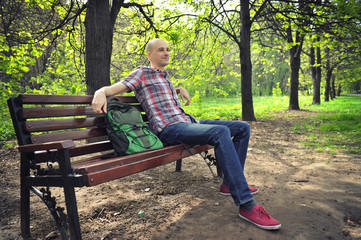 guy sits on a bench in park