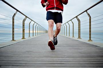 Sporty guy running along the pier