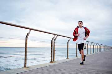 Sporty guy running along the pier