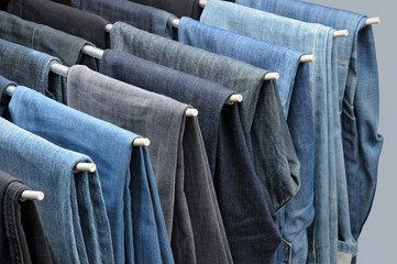 Colorful jeans hanging on hangers