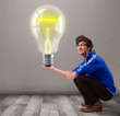 Attractive man holding realistic 3d light bulb