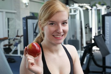 young beauty with a apple in a fitnessstudio