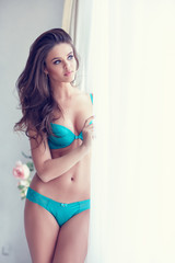 Beautiful alluring young woman in sexy turquoise lingerie