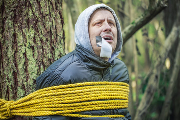 Man with tape on mouth tied to the tree in the woods