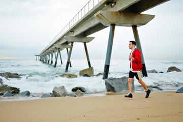 athlete man in sports a red windbreaker runs along the beach