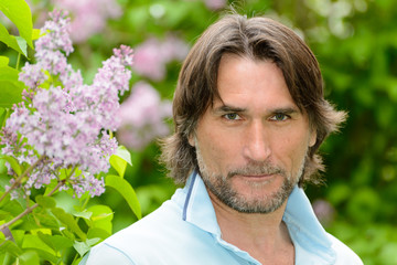 Middle-aged man near blooming lilacs
