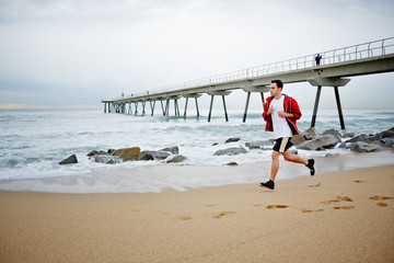 Young athlete man very quickly runs along the beach