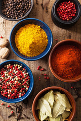 spices in bowls: pink black pepper, paprika powder, curry, bay l