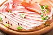 sliced prosciutto ham on chopping board with oregano and pepper