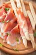 sliced prosciutto ham and grissini bread sticks