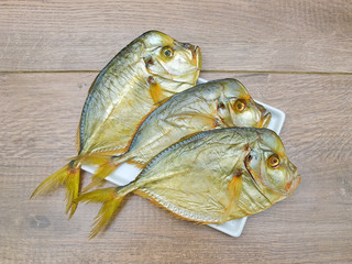 Vomero fish on a plate on a wooden background