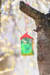Paper bird feeder on cherry tree in sunny day