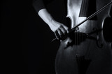 Fototapety Beautiful woman holding a cello with selective light and black d