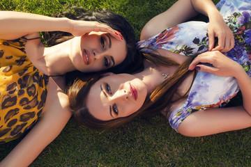 two beautiful women lying on green grass at garden