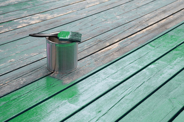 Wet painted wood in green, brush on a paint can