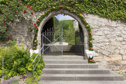 In de dag Begraafplaats Mit Blumen geschmückter Friedhofseingang