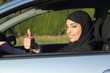 Happy arab saudi woman driving a car with thumb up - 65077080