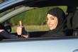 Leinwanddruck Bild - Happy arab saudi woman driving a car with thumb up