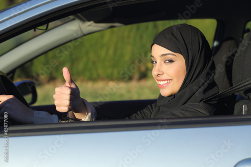 Leinwanddruck Bild Happy arab saudi woman driving a car with thumb up