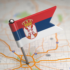 Serbia Small Flag on a Map Background.
