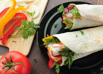 Wraps with fresh chicken and vegetables on a plate