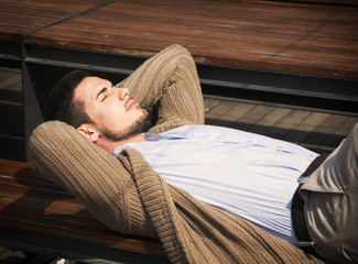 Attractive young man laying down on wood bench