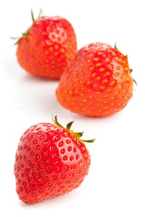 Three strawberries over white background