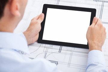 Businessman Holding Blank Digital Tablet Over Blueprint