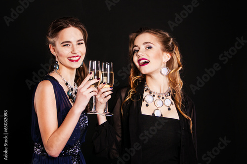 two stylish young women with glasses of champagne - 65082098