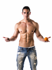 Muscular shirtless young man deciding: fruit or cookies