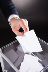 Businessman Inserting Ballot In Box On Desk