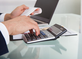 Businessman Calculating Expense In Office