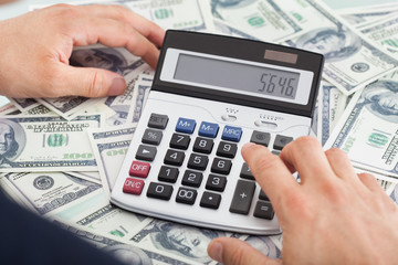 Businessman Calculating Money In Office