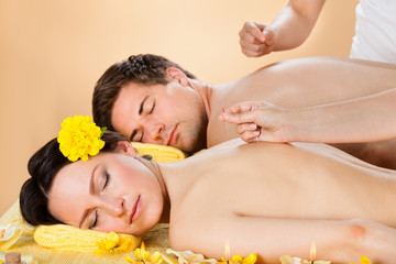 Couple Receiving Acupuncture Treatment At Spa
