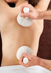 Woman Receiving Herbal Massage With Hot Balls At Spa