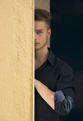 Attractive young blond man hiding half face behind wall