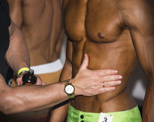 Bodybuilding competition backstage: contestant being oiled