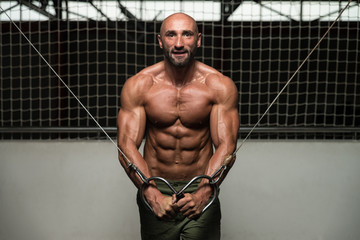 Muscular Bodybuilder Performing Cable Crossover