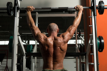 Bodybuilder Doing Heavy Weight Exercise For Shoulder