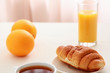 Croissants, Coffee, Orange Juice and Newspapers on table