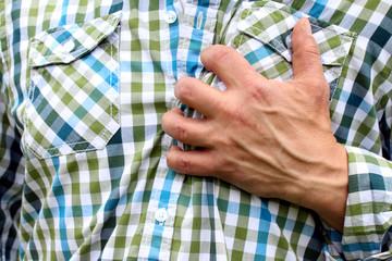 Mann hat Herzinfarkt fasst sich verkrampft an Brust
